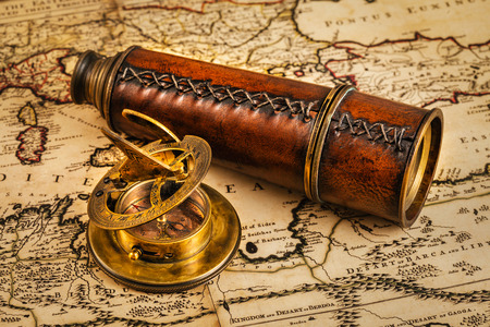sonnenuhr: Travel geography navigation concept background - old vintage retro compass with sundial and spyglass on ancient world map