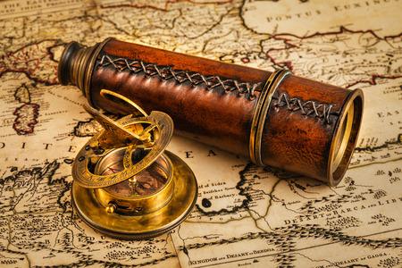 reloj de sol: Viajes geograf�a concepto de navegaci�n de fondo - viejo comp�s retro vendimia con el reloj de sol y catalejo en antiguo mapa del mundo