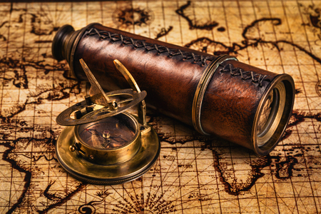 sundial: Travel geography navigation concept background - old vintage retro compass with sundial and spyglass on ancient world map
