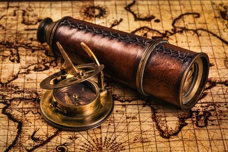 navegacion: Viajes geografía concepto de navegación de fondo - viejo compás retro vendimia con el reloj de sol y catalejo en antiguo mapa del mundo