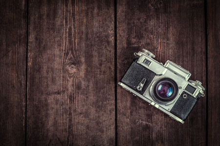 photography background: Photography concept  background - old retro vintage camera on grunge wooden texture