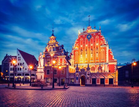 square image: Vintage retro effect filtered hipster style image of  Riga Town Hall Square, House of the Blackheads and St. Roland Statue illuminated in the evening twilight, Riga, Latvia Stock Photo
