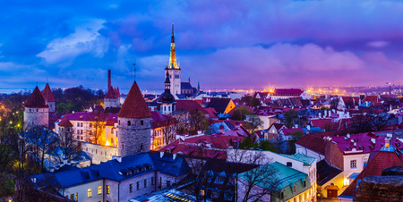 architectural heritage of the world: Panorama of aerial view of Tallinn Medieval Old Town with St. Olafs Church and Tallinn City Wall illuminated in twilight, Estonia