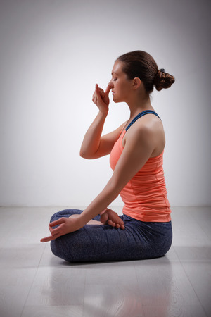 yogic: Beautiful sporty fit yogini woman practices pranayama breath control exercise in yoga asana Padmasana - lotus pose with Vishnu mudra in studio