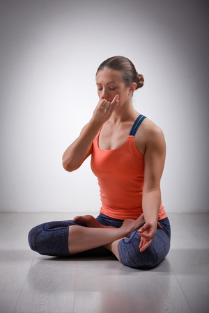 Beautiful sporty fit yogini woman practices pranayama breath control exercise in yoga asana Padmasana - lotus pose with Vishnu mudra in studio