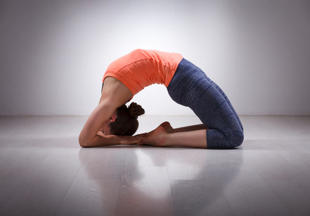 yogini: Beautiful sporty fit yogini woman practices yoga asana Kapotasana - pigeon pose intense backbend in studio