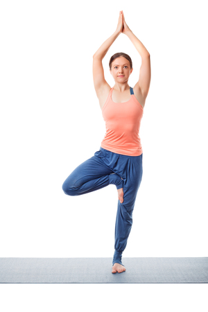 asana: Beautiful sporty fit yogini woman practices yoga asana Vrikshasana - tree pose isolated on white Stock Photo
