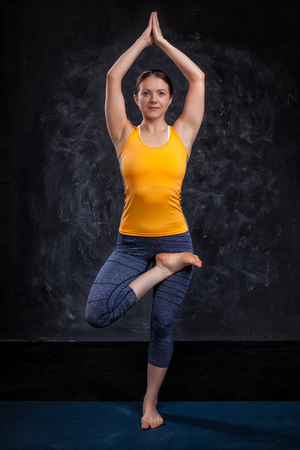 yogini: Beautiful sporty fit yogini woman practices yoga asana Vrikshasana - tree pose