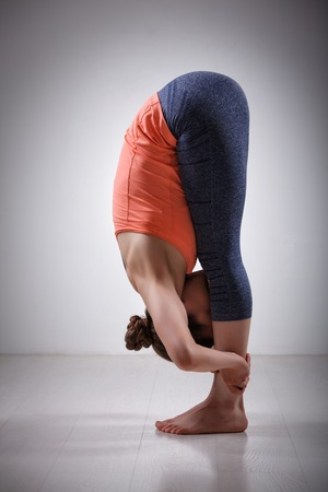 yogini: Beautiful sporty fit yogini woman practices yoga asana Uttanasana - standing forward bend pose