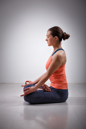 yogini: Beautiful fit yogini woman meditating  in yoga asana Padmasana (Lotus pose) cross legged position for meditation with Chin Mudra - psychic gesture of consciousness