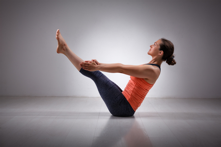 yogini: Beautiful sporty fit yogini woman practices yoga asana Paripurna navasana - boat pose