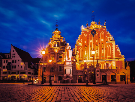 square image: Vintage retro effect filtered hipster style image of Riga Town Hall Square, House of the Blackheads and St. Roland Statue illuminated in the evening twilight, Riga, Latvia