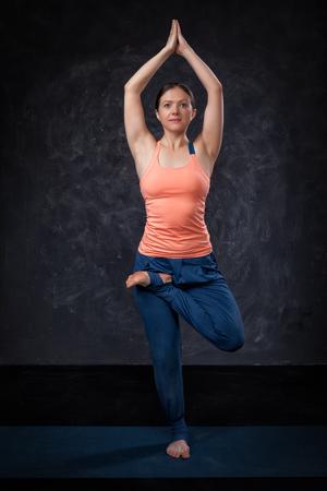 yogini: Beautiful sporty fit yogini woman practices yoga asana Vrikshasana - tree pose