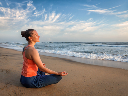 yoga meditation: Young sporty fit woman doing yoga - meditating and relaxing in Padmasana Lotus Pose) with chin mudra outdoors at tropical beach on sunset
