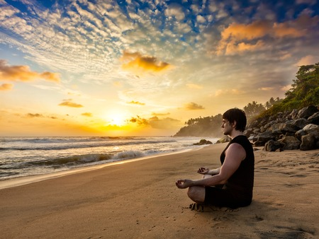 yogic: Young sporty fit man doing yoga meditating in padmasana lotus pose on tropical beach on sunset