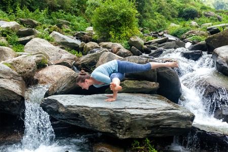 eka: Young sporty fit woman doing yoga asana Eka Pada Koundinyasana 1 at tropical waterfall