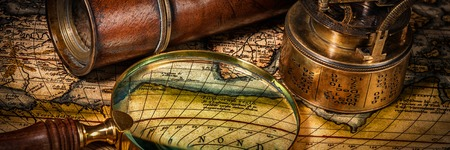 navigational: Travel geography navigation concept background - letterbox panorama of old vintage retro compass with sundial, spyglass and magnifying glass on ancient world map Stock Photo
