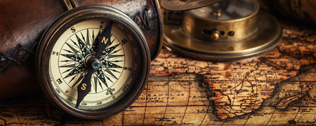 Travel geography navigation concept background - letterbox panorama of old vintage retro compass with sundial, spyglass and rope on ancient world map Archivio Fotografico