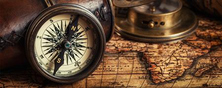 Reizen aardrijkskunde navigatie concept achtergrond - brievenbus panorama van oude vintage retro kompas met zonnewijzer, verrekijker en touw op de oude kaart van de wereld