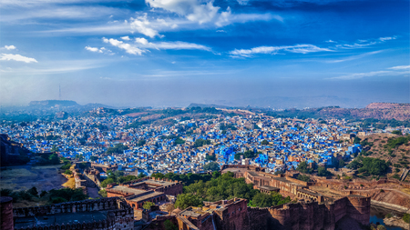 Aerial  panorama of Jodhpur, also known as Blue City due to the vivid blue-painted Brahmin houses. View from Mehrangarh Fort (part of fortifications is also visible).  Jodphur, Rajasthan, India Stock Photo