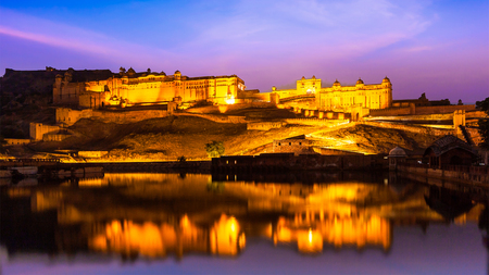 amber fort: Panorama of Amer Fort (Amber Fort) illuminated at night - one of principal attractions in Jaipur, Rajastan, India refelcting in Maota lake in twilight
