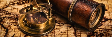 sun dial: Travel geography navigation concept background - letterbox panorama of old vintage retro compass with sundial and spyglass on ancient world map