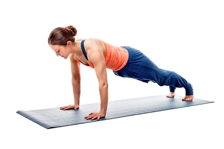 hatha: Young fit sporty woman doing Hatha yoga asana Utthita chaturanga dandasana - extended four-limbed staff (plank) pose isolated Stock Photo