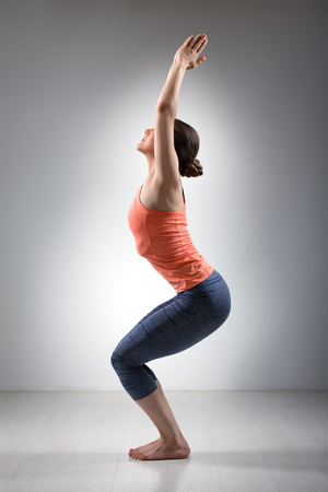hatha: Sporty fit woman doing Surya Namaskar ashtanga vinyasa yoga asana Utkatasana - chair pose Stock Photo