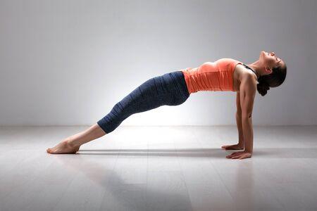 hatha: Beautiful sporty fit yogini woman practices Ashtanga Vinyasa yoga asana Purvottanasana - upward-facing plank full pose