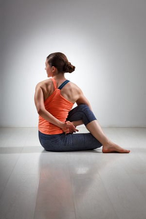 yogini: Beautiful sporty fit yogini woman practices yoga asana ardha matsyendrasana - half spinal twist pose Stock Photo