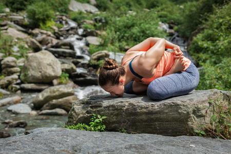 baddha: Young sporty fit woman doing yoga - meditating in Baddha Padmasana (Bound Lotus Pose) outdoors at tropical waterfall