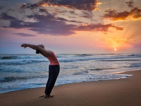 Young sporty fit woman doing yoga Sun salutation Surya Namaskar pose Hasta Uttanasana on tropical beach on sunset Stock Photo