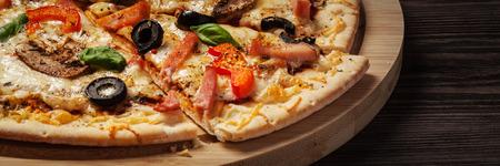 Letterbox Panorama der Schinken in Scheiben geschnitten Pizza mit Paprika und Oliven auf Holzbrett auf dem Tisch Standard-Bild - 47718388