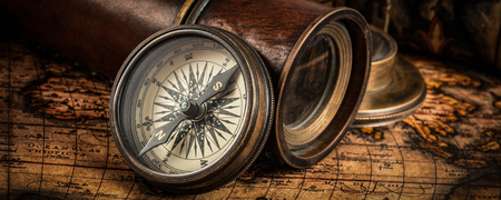 sun dial: Travel geography navigation concept background - letterbox panorama of old vintage retro compass with sundial, spyglass and rope on ancient world map Stock Photo