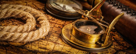 sundial: Travel geography navigation concept background - panorama of old vintage retro compass with sundial, spyglass and rope on ancient world map Stock Photo