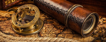sundial: Travel geography navigation concept background - letterbox panorama of old vintage retro compass with sundial and spyglass on ancient world map