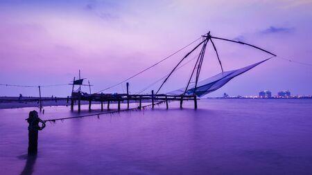 kochi: Panorama of Kochi tourist attraction - chinese fishnets on sunset with grunge texture overlaid. Fort Kochin, Kochi, Kerala, India
