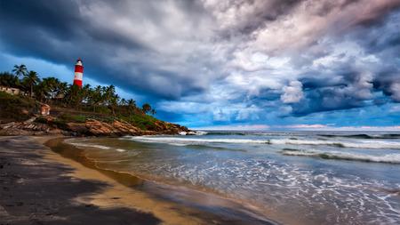 kovalam: Panorama of gathering storm on beach and Kovalam (Vizhinjam) lighthouse on stormy sunset. Kerala, India