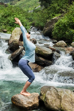 standing stone: Young sporty fit woman doing yoga asana Utkatasana (chair pose) outdoors at tropical waterfall standing on stone
