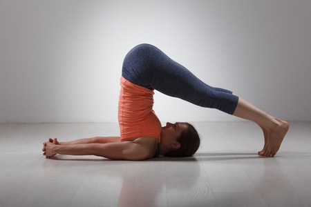 yogini: Beautiful sporty fit yogini woman practices yoga asana Halasana - plow pose