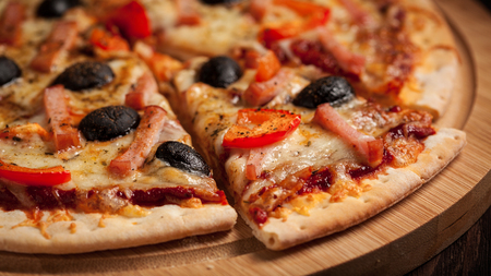 pizza: Letterbox panorama of sliced ham pizza with capsicum and olives on wooden board on table