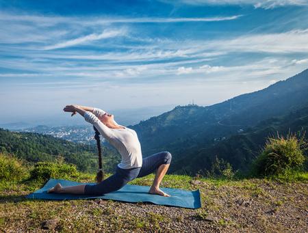 スポーティなフィット女性ヨガ Anjaneyasana - 朝山で屋外低三日月突進ポーズ 写真素材