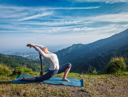 Sporty fit woman practices yoga Anjaneyasana - low crescent lunge pose outdoors in mountains in morning
