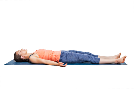 yogini: Beautiful sporty fit yogini woman relaxes in yoga asana Savasana - corpse pose in studio Stock Photo