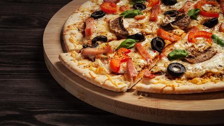 トウガラシとテーブルの上の木の板には、オリーブのスライスしたハム ピザのレター ボックス パノラマ 写真素材