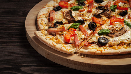 Letterbox panorama of sliced ham pizza with capsicum and olives on wooden board on table