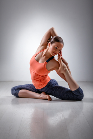 yogini: Beautiful sporty fit yogini woman practices yoga asana Eka pada rajakapotasana - one-legged pigeon pose in studio