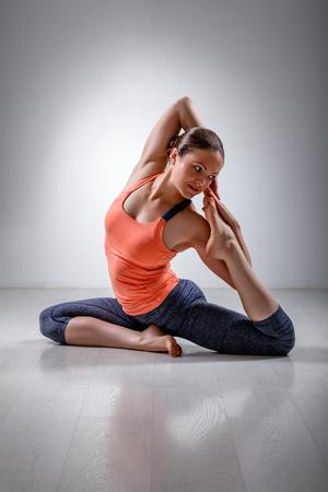 hatha: Beautiful sporty fit yogini woman practices yoga asana Eka pada rajakapotasana - one-legged pigeon pose in studio