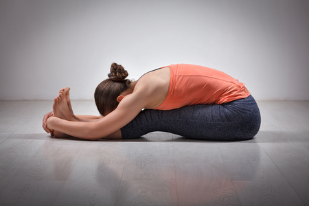 ashtanga: Sporty fit woman practices Ashtanga Vinyasa yoga back bending asana Paschimottanasana - seated forward bend Stock Photo