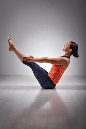 yogic: Beautiful sporty fit yogini woman practices yoga asana Paripurna navasana - boat pose
